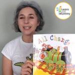Una donna con una maglietta bianca mostra un libro inb inglese per bambini dal titolo All Change scritto da Ian Whybrow e illustrato da David Melling