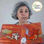 una donna mostra un libro illustrato in inglese per bambini che raffigura un koala e un canguro