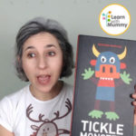 teacher letizia indossa una maglietta bianca e mostra il libro in inglese per bambini intitolato tickle monster di Edouard Manceau