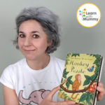 a woman with a white tshirt show a picture book titled monkey puzzle by julian Donaldson