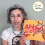 teacher letizia indossa una maglietta bianca e mostra il libro in inglese per bambini intitolato Ahhchoo illustrato da Ardoq della serie Learn with Mummy in the Rockies