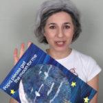 teacher letizia indossa una maglietta bianca e mostra il libro in inglese per bambini intitolato Papa please get the moon for me di Eric Carle